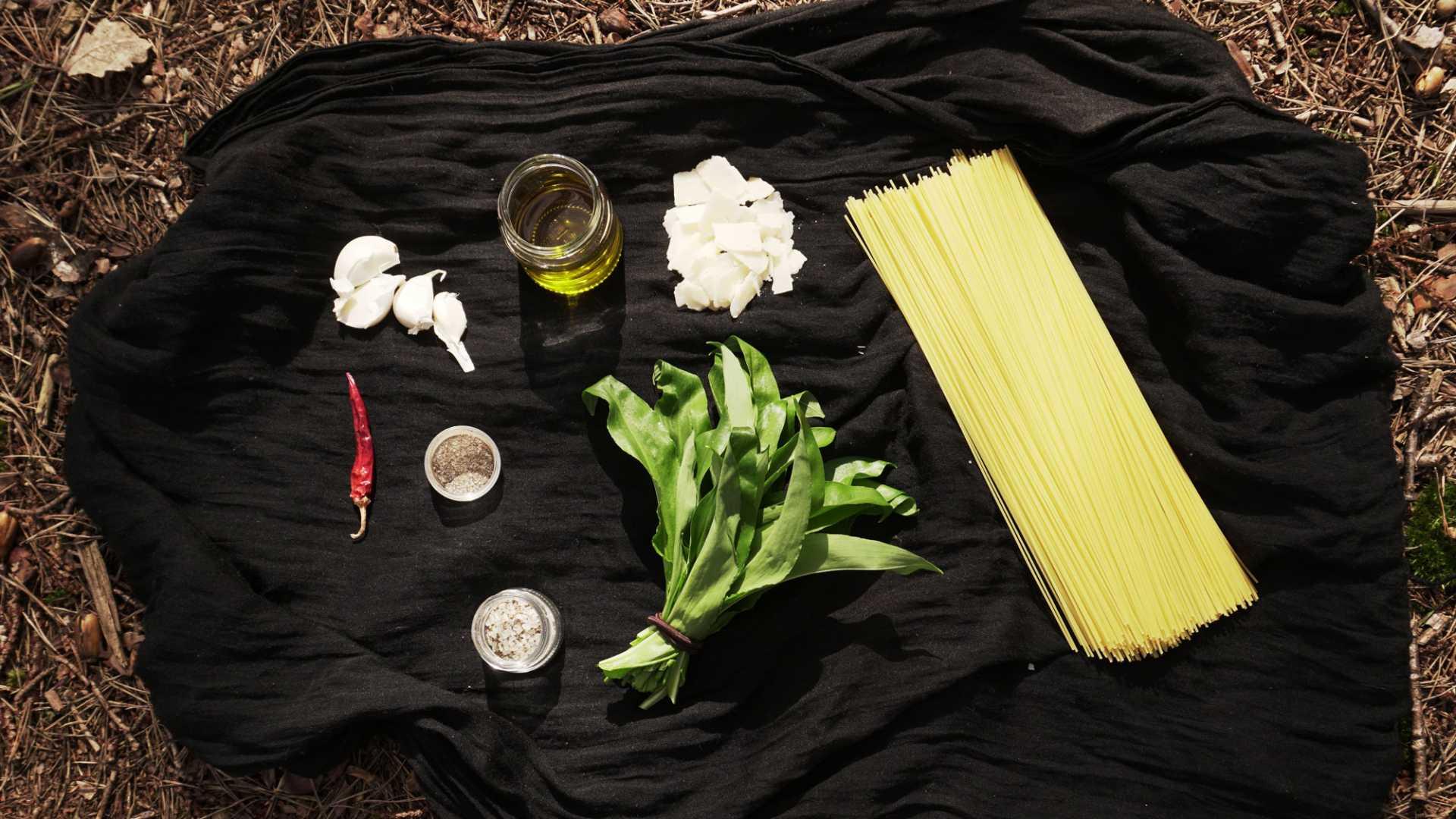 Zutaten für Bärlauch-Spaghetti liegen auf Waldboden