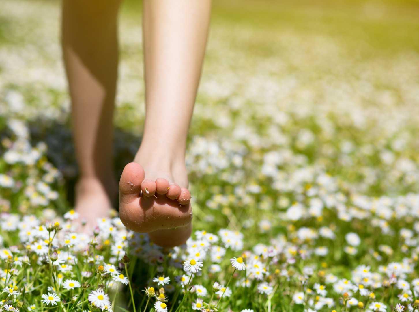 Junge läuft barfuß über Wiese mit Gänseblümchen
