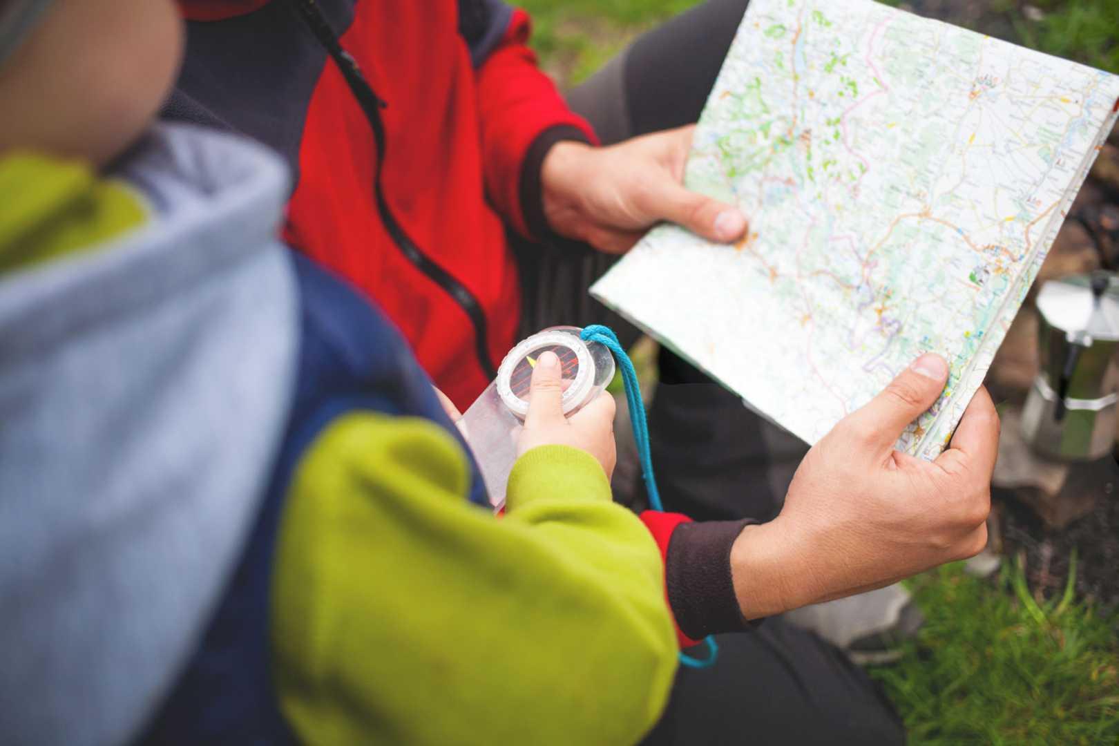 Kind beim Wandern mit Kompass in der Hand schaut auf eine Karte, die von einer anderen Person gehalten wird.