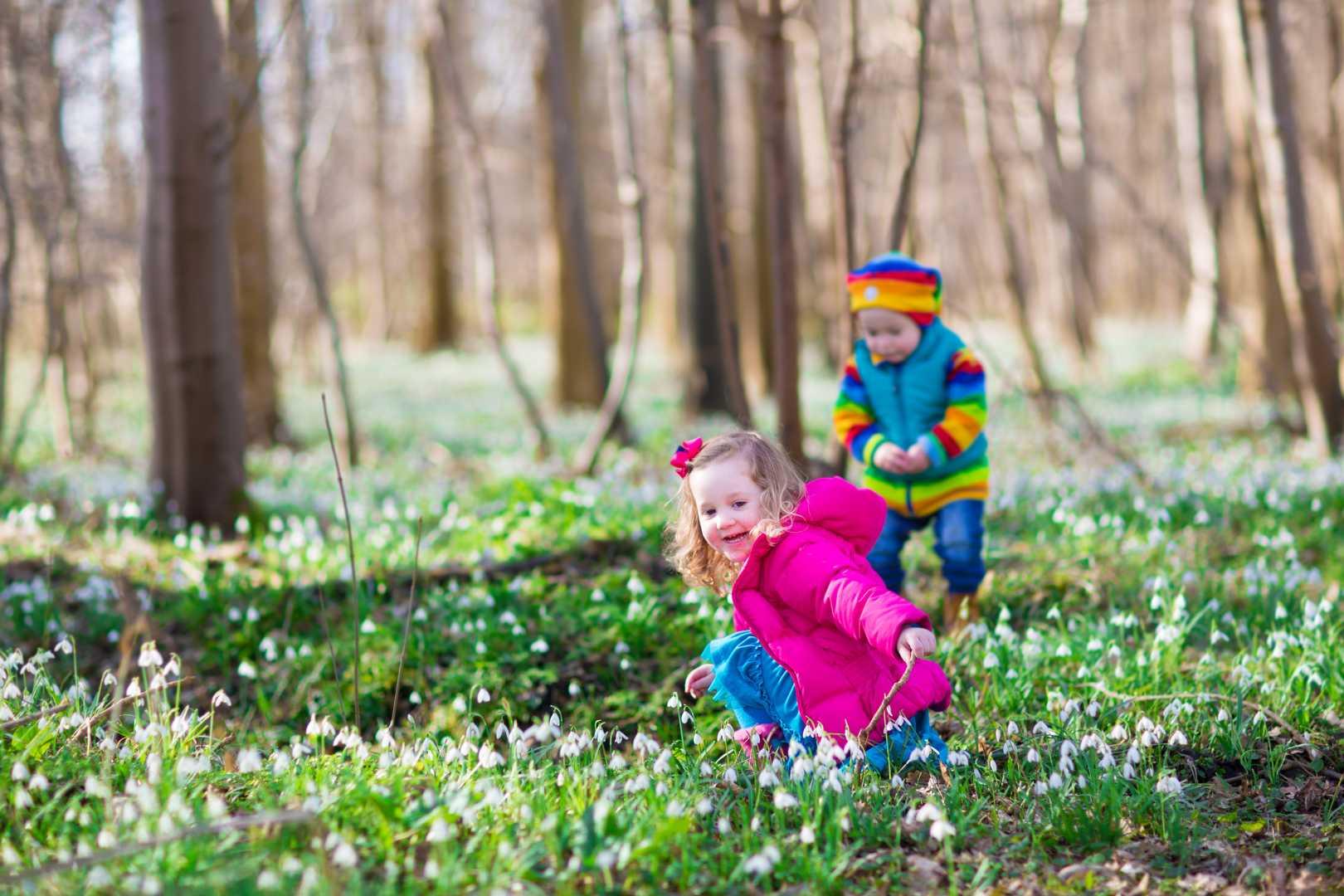zwei Kinder spielen im Wald in Schneeglöckchen