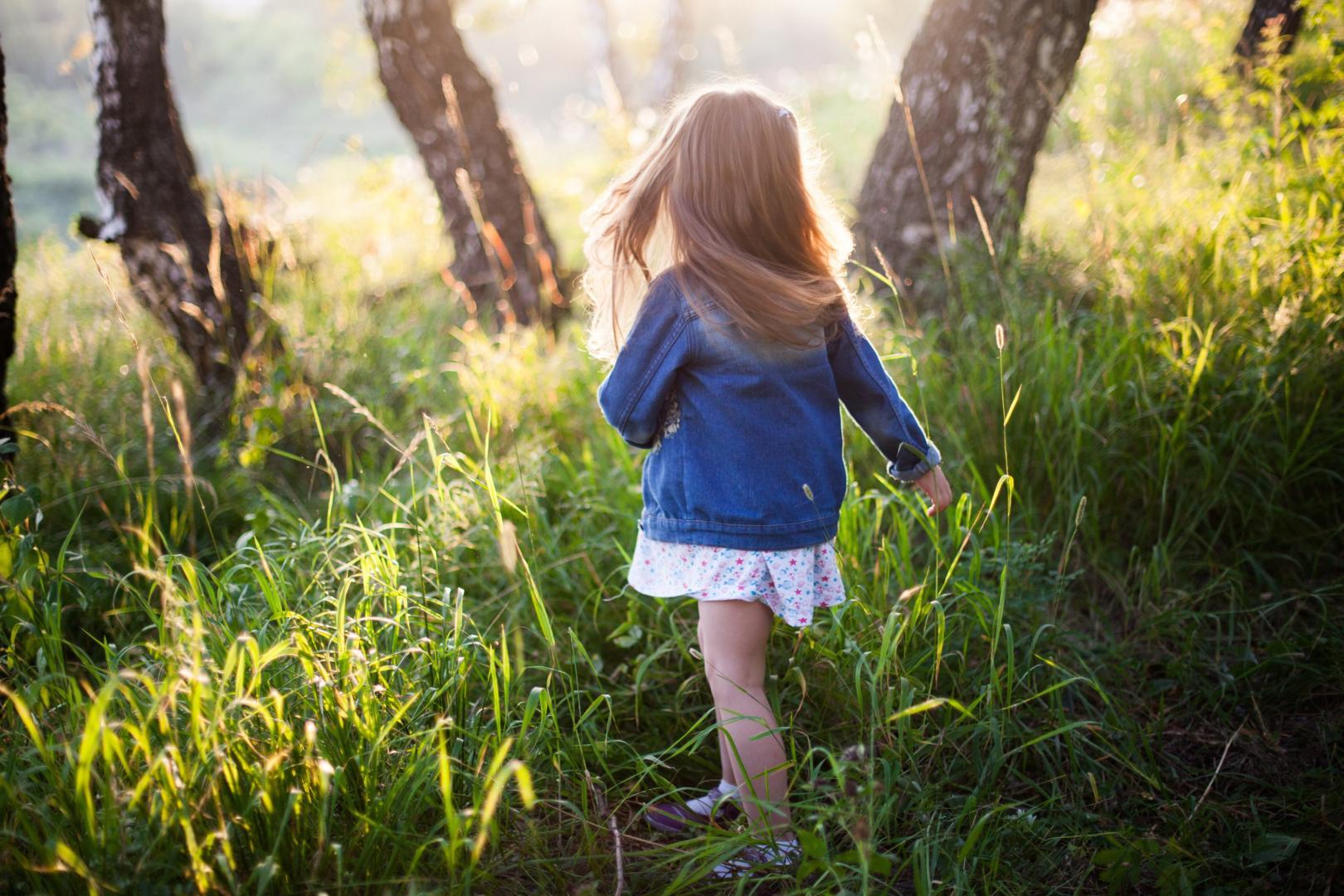 Mädchen läuft mit nackten Beinen durch hohes Gras