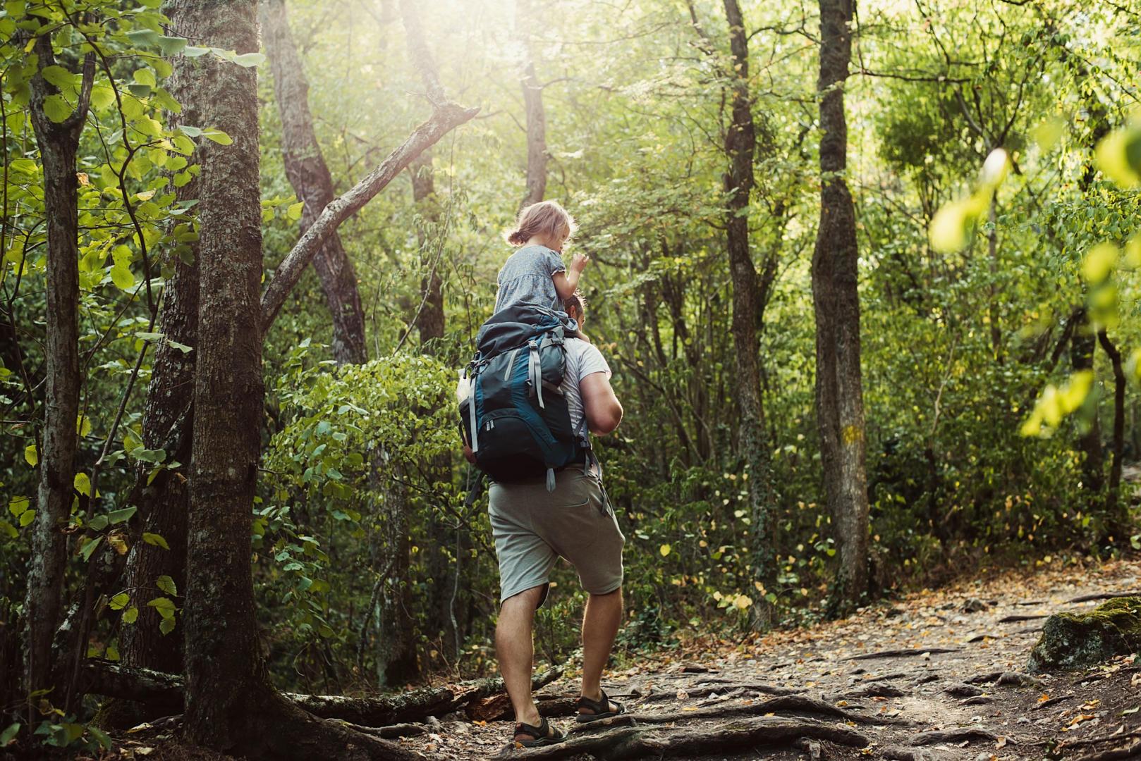 Mädchen von hintern, das auf den Schultern eines Mannes durch den Wald getragen wird.