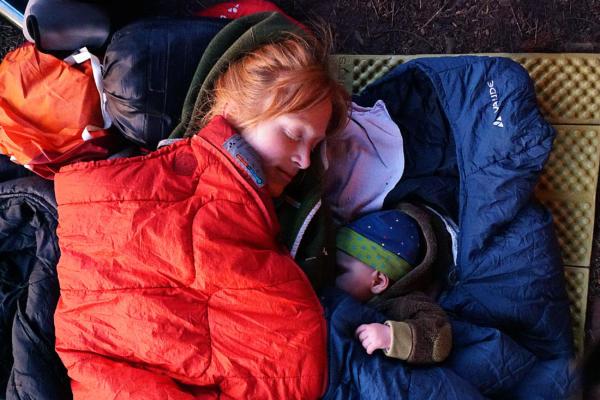 Mutter mit Baby im Schlafsack bei Biwakieren