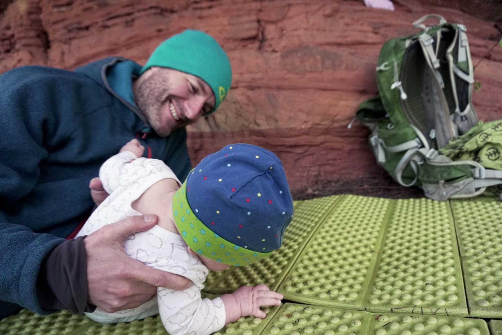 Vater mit Baby auf Isomatte beim Biwakieren