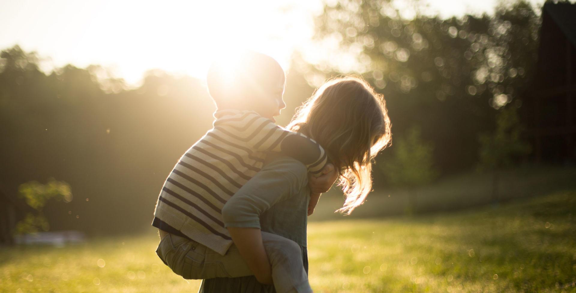 Ein Kind trägt ein anderes Huckepack vor'm Sonnenuntergang