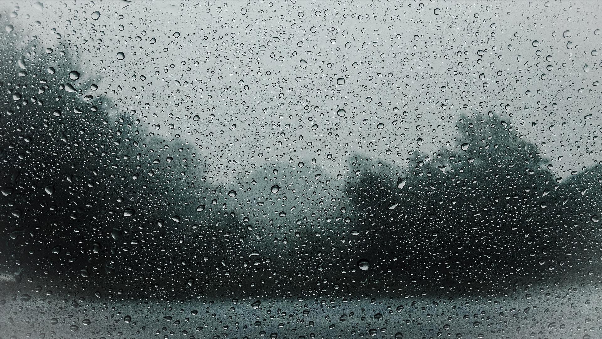 Landschaft hinte einer Glasscheibe bei Regen