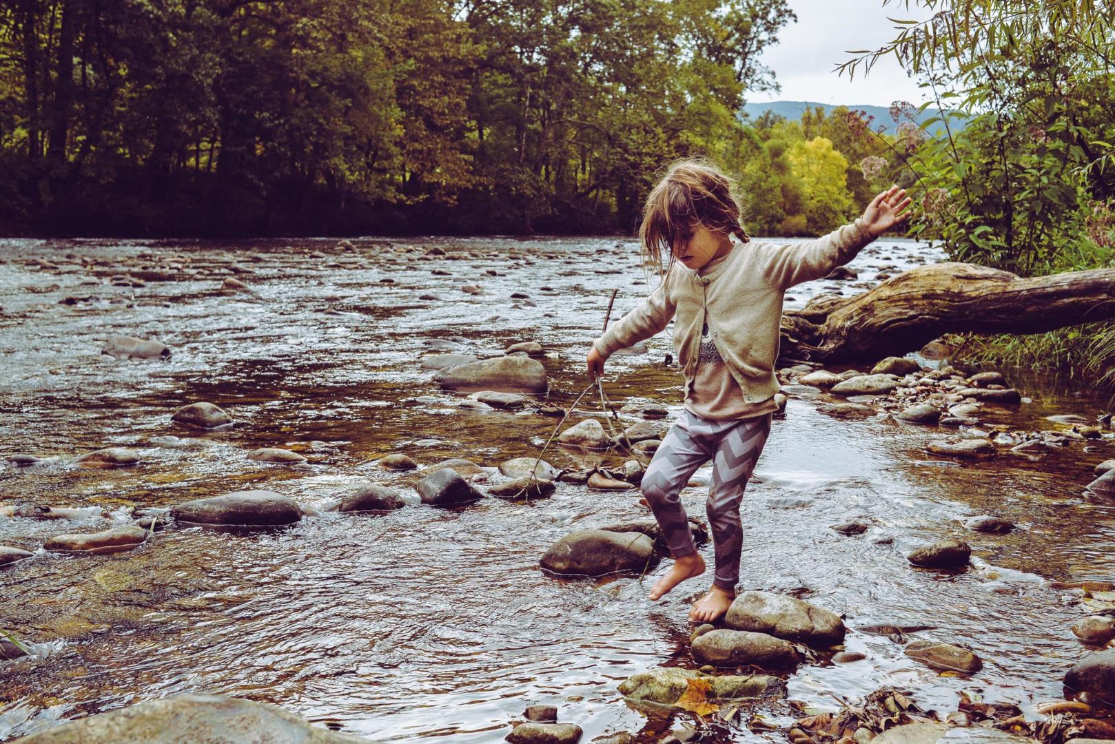 Mädchen balanciert auf Steinen an einem Bach