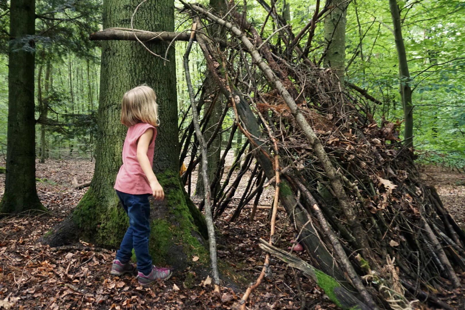 Selbstgebaute Waldhütte mit Mädchen