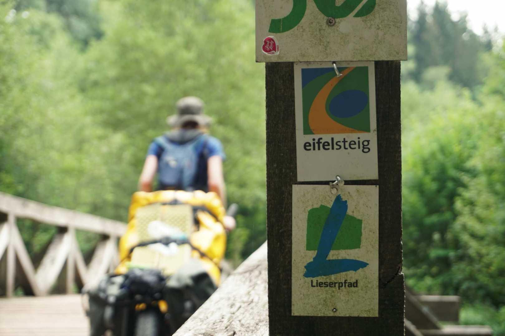 Jana fährt über eine Brücke mit dem Monowalker. Im Vordergrund markieren zwei Schilder den Eifelsteig und den Lieserpfad