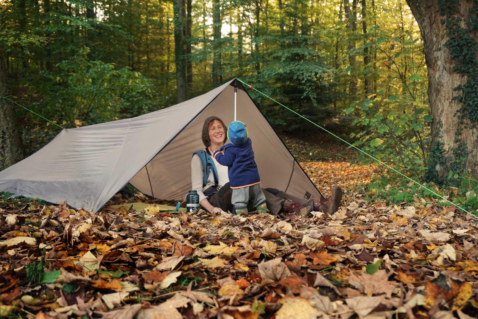Jana und der Kleine in einem Tarp, dass als Zeltdach aufgebaut ist