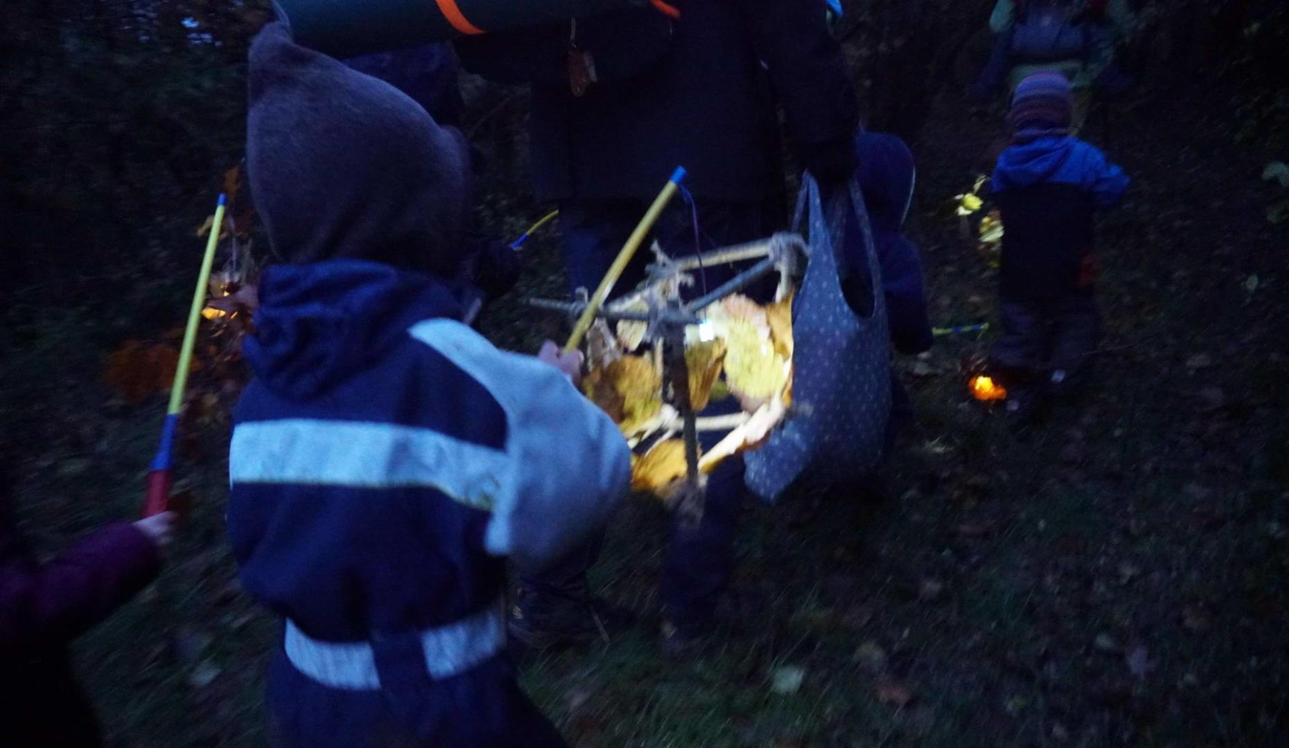 Kinder gehen mit selbst gebastelten laternen durch den Wald