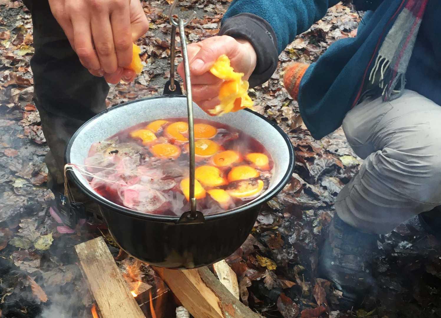 Orangen auspressen in den Winter Punsch über dem Lagerfeuer