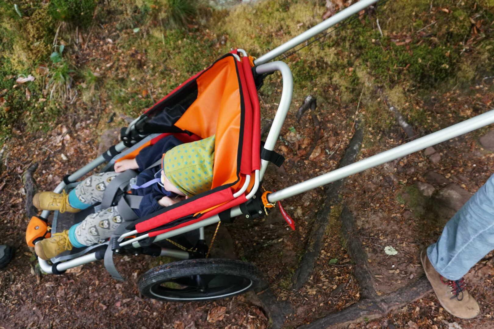 Kind liegt im Hike Kid Gelände Kinderwagen