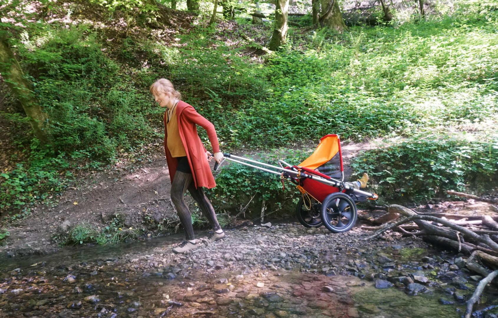 Jana Heck zieht den Hike Kid durch einen Bach