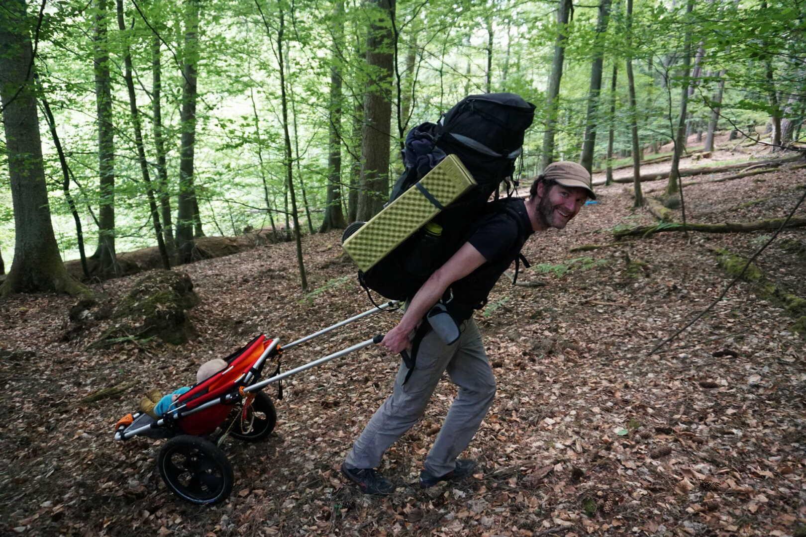 Patrick Heck zieht den Hike Kid Oudoor Kinderwagen mit Rucksack auf dem Rücken durch den Wald